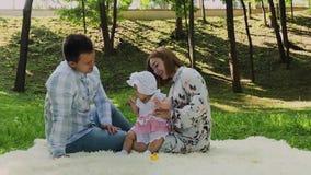 Mamma felice e papà della famiglia che giocano con il bambino sul copriletto stock footage