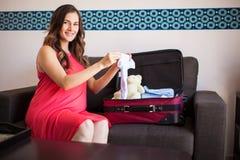 Mamma futura sveglia che imballa una valigia Fotografia Stock