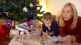 Mamma gelezen boek met zoon onder een nieuwe jaarboom stock videobeelden