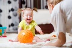Mamma het spelen bal met baby binnen Stock Fotografie