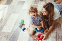 Mamma het spelen met zoon op een vloer royalty-vrije stock afbeelding