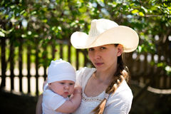 Mamma i en cowboyhatt som rymmer hans unga son på naturen Royaltyfri Foto