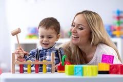 Mamma of leraar playng met jong geitjepeuter in kinderdagverblijf stock foto's