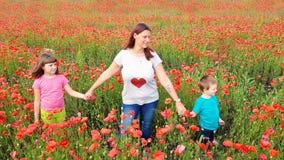 Mamma med barn i ett fält av vallmo Fotografering för Bildbyråer