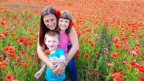 Mamma med barn i ett fält av vallmo Royaltyfri Foto