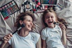 Mamma med dottern som gör makeup royaltyfria foton