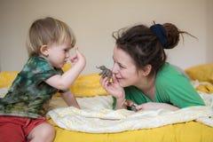 Mamma med dreadlocks och hennes lilla son som spelar på sängen med t arkivbilder