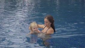 Mamma med engammal dotter i hotellpöl nära havet stock video