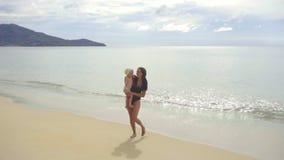 Mamma med engammal dotter som promenerar den sandiga stranden stock video