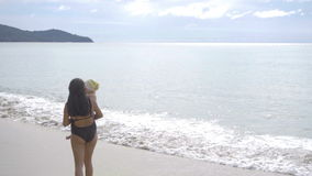 Mamma med engammal dotter som promenerar den sandiga stranden lager videofilmer