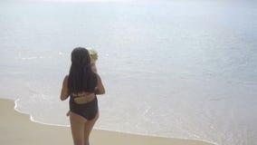Mamma med engammal dotter som promenerar den sandiga stranden arkivfilmer