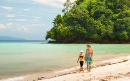 Mamma med hennes dotter som kommer längs stranden royaltyfria bilder