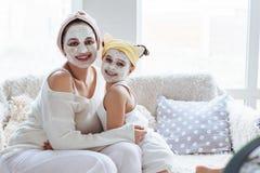 Mamma med hennes maskering för framsida för dotterdanandelera royaltyfri foto