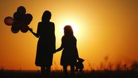 Mamma med skeppsdockast?llningen p? solnedg?ngen H?ll bollar och leksakbj?rnen royaltyfria bilder