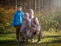 Mamma med två barn som går i höstskogen royaltyfria bilder