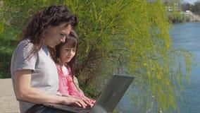 Mamma met baby met laptop in openlucht Het mamma leert een dochter op de rivierbank Een vrouw met een baby in de verse lucht stock video