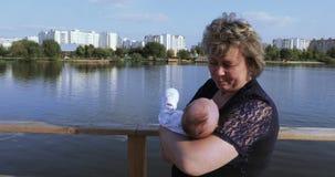 Mamma met dochter op vijver stock video