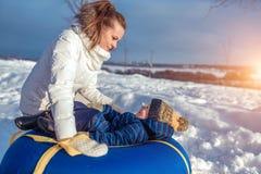 Mamma met een jongenszoon 3 jaar oud, in de winter in een paar op een heuvel, verse lucht De stadspark van het vakantieweekend Zi royalty-vrije stock afbeelding