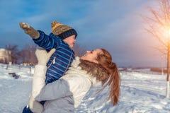 Mamma met een jongenszoon 3 jaar oud, in de winter in een paar op een heuvel, verse lucht De stadspark van het vakantieweekend Zi stock foto