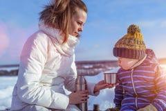 Mamma met een jongenszoon 3 jaar oud, in de winter in een paar in de verse lucht De rust neemt in het weekend, op de bank, a zijn royalty-vrije stock afbeeldingen