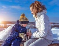 Mamma met een jongenszoon 3 jaar oud, in de winter in een paar in de verse lucht De rust neemt in het weekend, op de bank, a zijn stock afbeelding