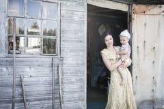 Mamma met een kind op de portiek van een huis in het dorp royalty-vrije stock foto