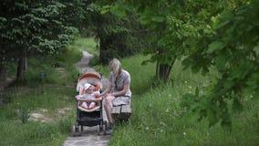 Mamma met een kleine dochter die in een park op een bank rusten Het éénjarige kind zit in een vervoer en speelt stock video
