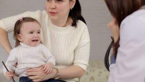 Mamma met een weinig schreeuwende dochter bij de ontvangst bij de pediater stock videobeelden