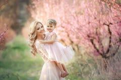 Mamma met een zuigeling in de roze tuin met bloemenbomen stock fotografie