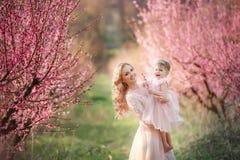 Mamma met een zuigeling in de roze tuin met bloemenbomen stock afbeelding