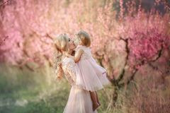 Mamma met een zuigeling in de roze tuin met bloemenbomen stock foto