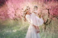 Mamma met een zuigeling in de roze tuin met bloemenbomen royalty-vrije stock fotografie