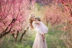 Mamma met een zuigeling in de roze tuin met bloemenbomen royalty-vrije stock afbeelding
