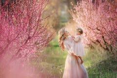 Mamma met een zuigeling in de roze tuin met bloemenbomen royalty-vrije stock afbeeldingen
