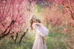 Mamma met een zuigeling in de roze tuin met bloemenbomen stock foto's