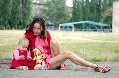 Mamma met haar dochter en pop Stock Foto