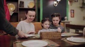 Mamma met haar twee dochters die in de koffie spreken terwijl de kelner op het lijstbestek zet stock videobeelden