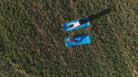 Mamma met haar weinig dochter het uitrekken zich op de mat op het gebied in warme de zomerdag Lucht panorama stock footage