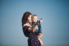 Mamma met kind in haar wapens tegen de blauwe hemel Royalty-vrije Stock Afbeeldingen