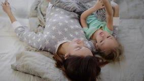 Mamma met kort zwart haar, die grijze pyjama's met sterren op het bed met een licht linnen dragen Vrouw die haar dochter koestert stock footage