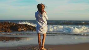 Mamma met lachende weinig dochter in haar wapens die op het zand oceaanstrand spinnen stock videobeelden