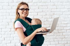 Mamma met laptop holding pasgeboren in babyslinger royalty-vrije stock foto