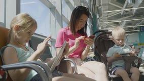Mamma met twee kinderen, die gadgets gebruiken om op vertrek in de wachtkamer bij de luchthaven te wachten stock videobeelden