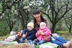 Mamma met tweelingen op plaid openlucht in appeltuin Royalty-vrije Stock Afbeelding