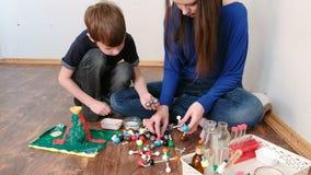 Mamma met zoon de modellen van de de bouwmolecule van gekleurde plastic bouwreeks stock footage