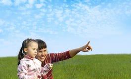 Mamma mit einem Kind, das auf dem Feld spielt Lizenzfreie Stockbilder