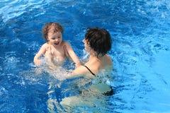 Mamma mit Schätzchen im Pool stockfoto