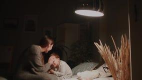 Mamma nella camera da letto della sua casa che prova a mettere per inserire il piccolo figlio archivi video