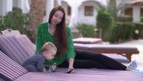 Mamma och att behandla som ett barn klockavideoen på smartphonen med entusiasm i ultrarapid stock video