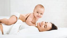 Mamma och att behandla som ett barn pojken i blöjan som spelar i sovrum royaltyfria foton